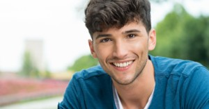 Young smiling man who uses athletic mouthguards
