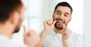 Man flossing teeth before a check up